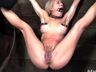 Beautiful blonde in bondage having her tits oiled in BDSM shoot